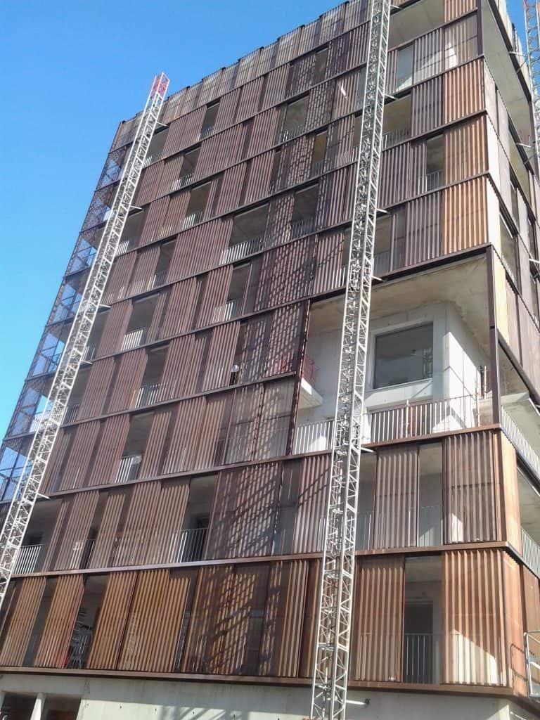 Vue en contreplongée d'un bâtiment au bardage rouge sur l'île de Nantes réalisé par les Ateliers David