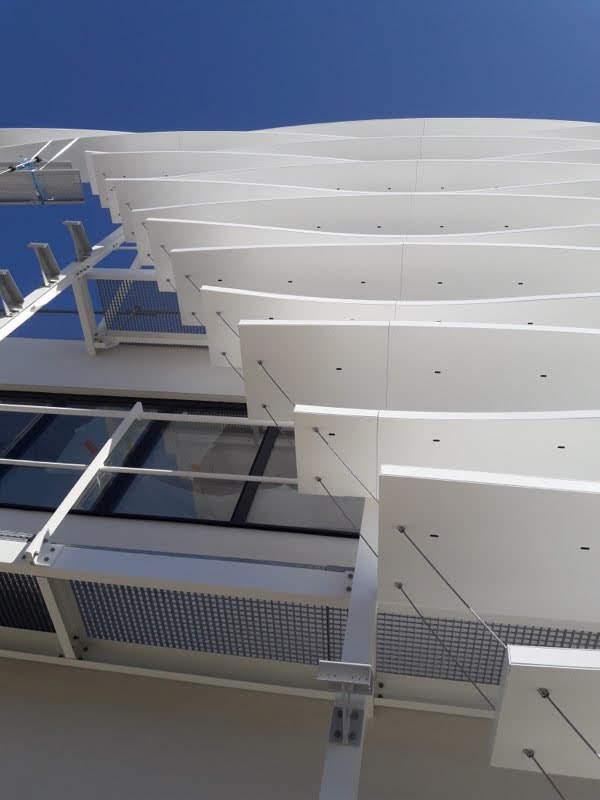 Vue en contreplongée de la mise en place des lames brises soleil effectuée par les Ateliers David