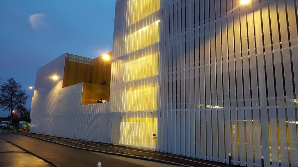 Vue extérieure du nouveau Parking Relais La Neustrie habillé d'un bardage blanc et jaune réalisé et posé par les Ateliers David