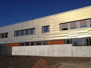 Habillage d'une façade du Lycée Feyder d'Epinay-Sur-Seine avec un bardage coques BS et lames Chaotic en Gold PERLA